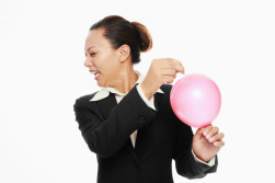 woman looking away anxiously as she is about to pop balloon. Symbolizes title of post, The Souffle and The Sledgehammer