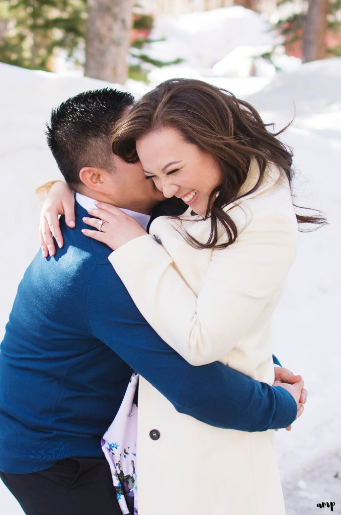 Engaged couple laughing in the snow