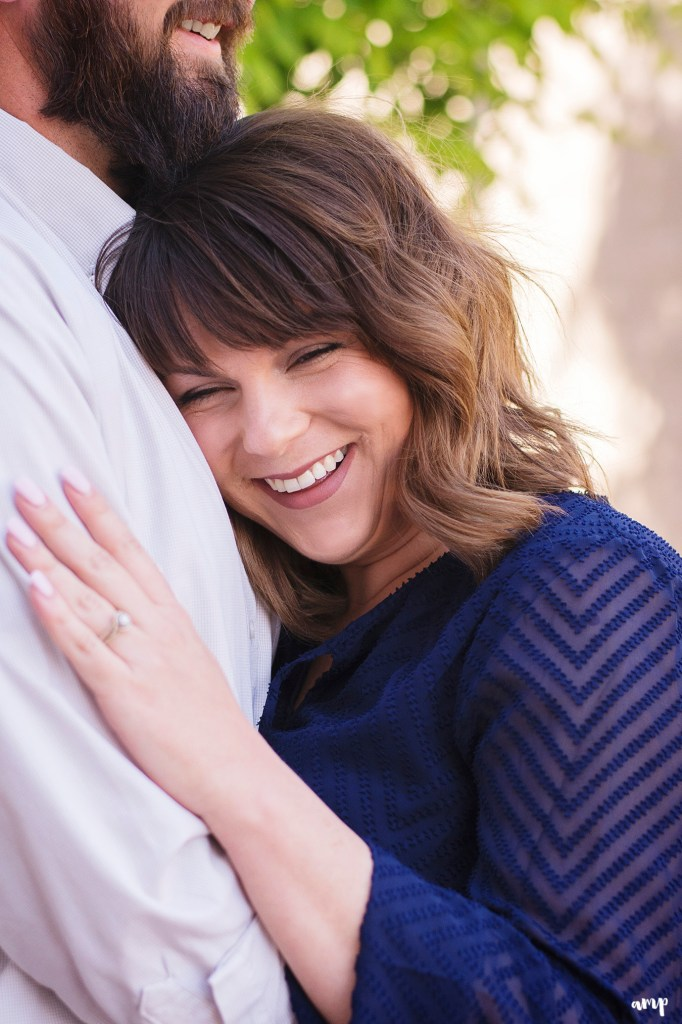 Woman laughing as she snuggles against her fiance's chest