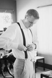 Groom doing up his suspenders