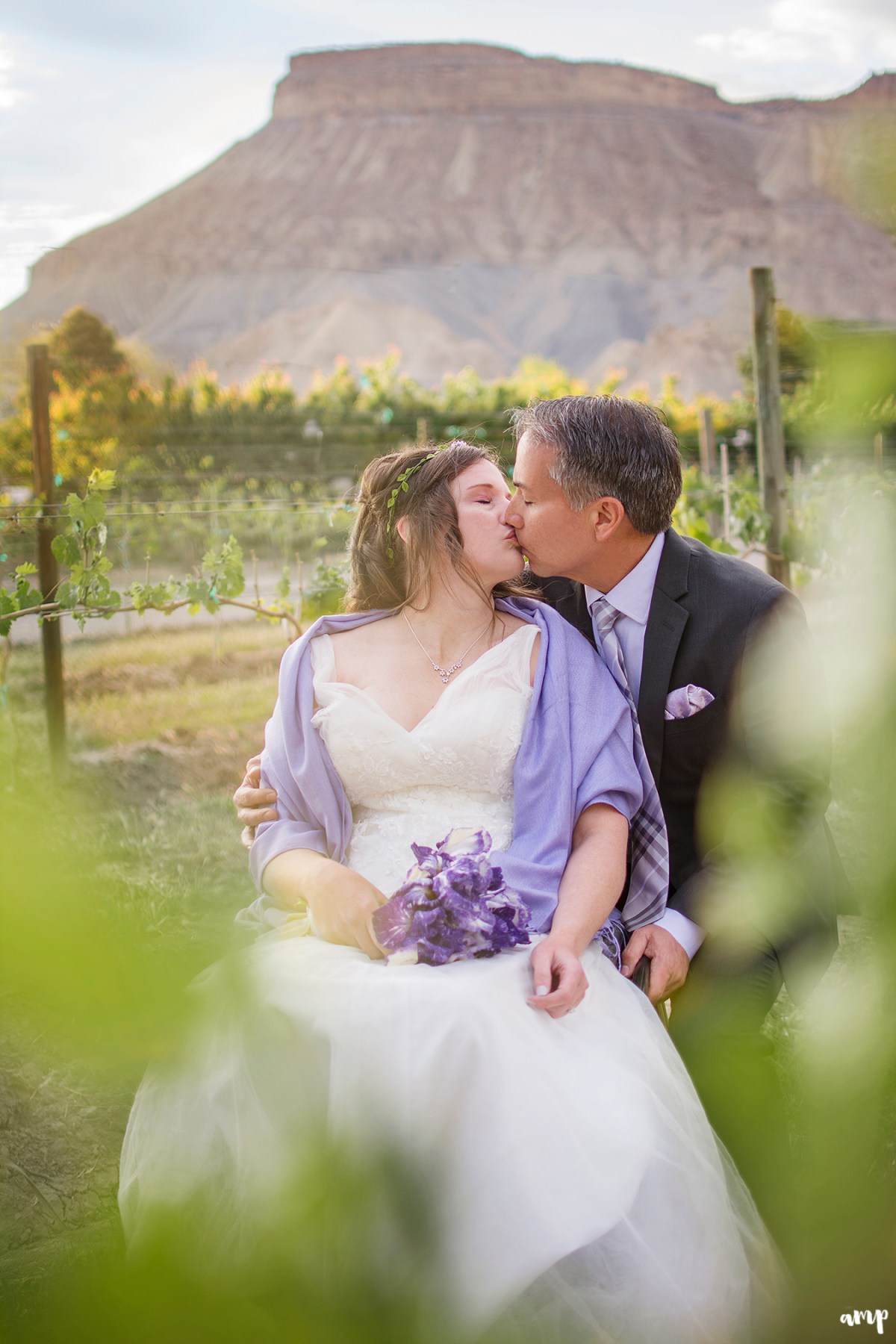 Couple kissing in a vineyard with Mt. Garfield in the distance