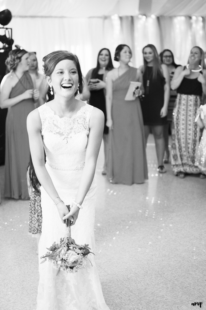 Bride laughing during wedding bouquet toss