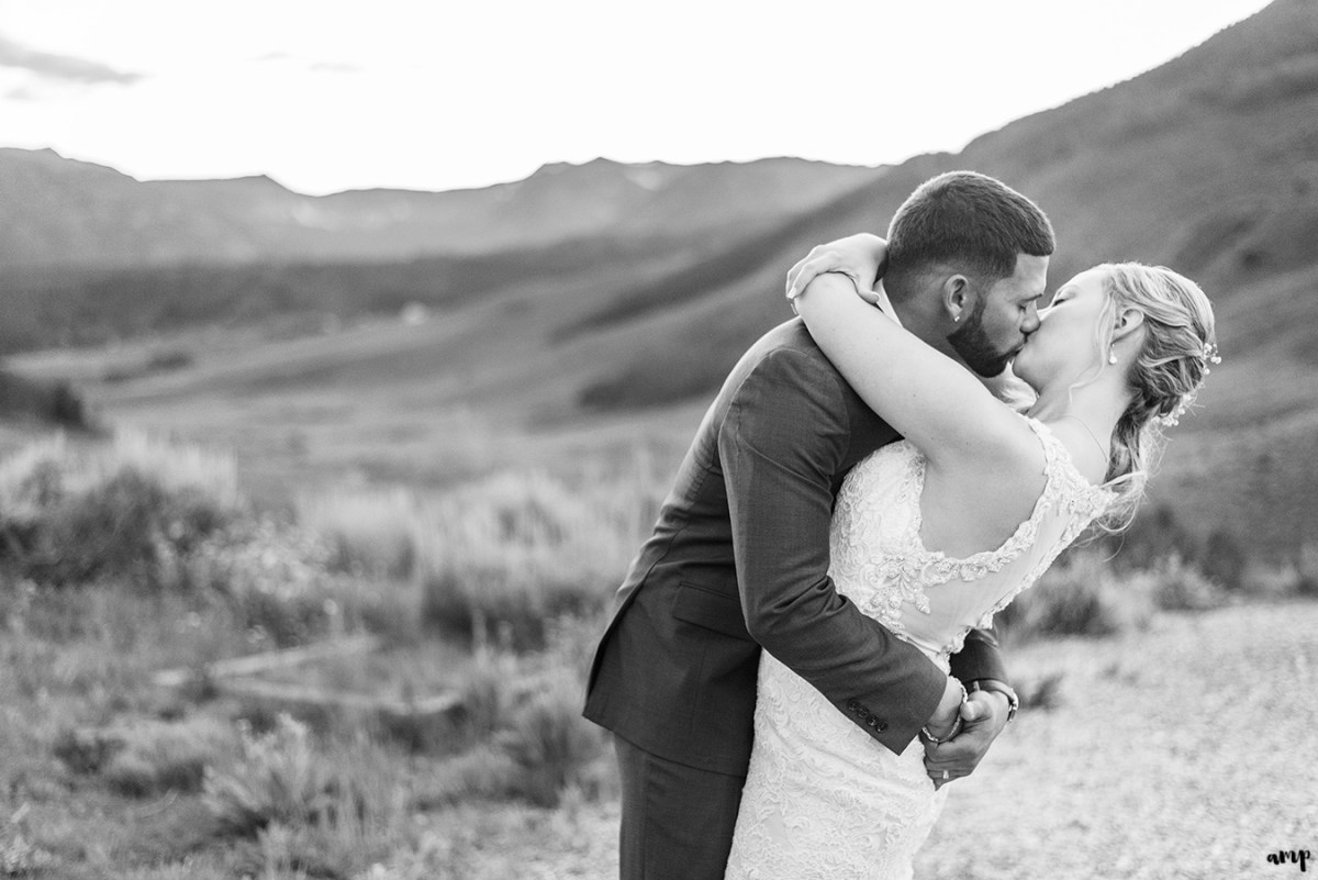 Bride and groom kissing with Crested Butte in background