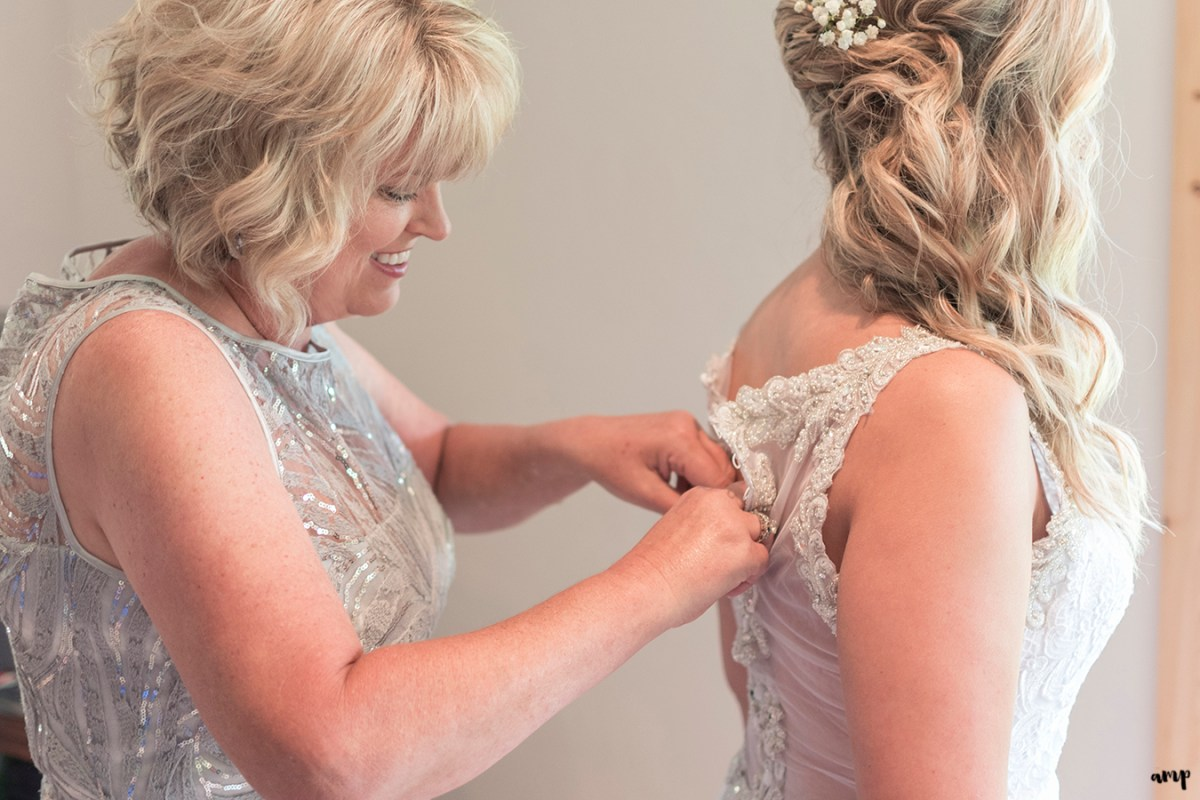 Bride's mother helping her do up the wedding dress