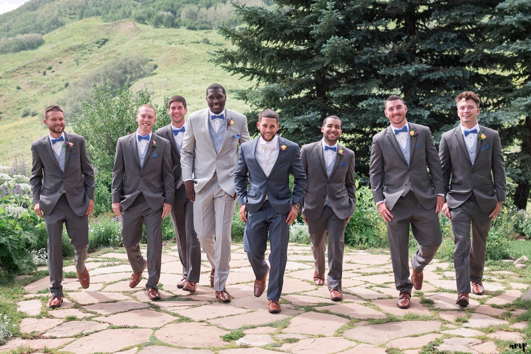 Groomsmen walking toward the camera with mountains in the back