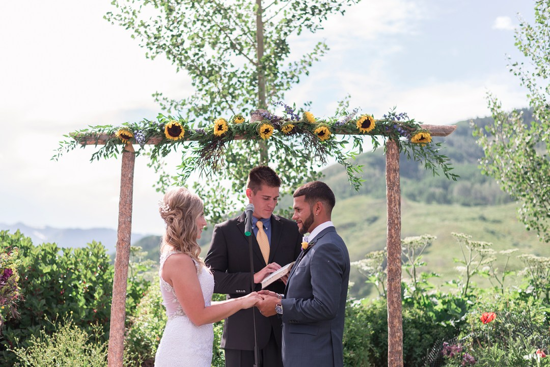 Bride and groom at the wooden arch altar of the Crested Butte Mountain Wedding Garden