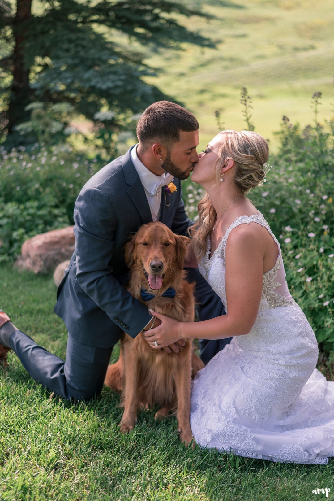 Bride and groom share a kiss over their dog