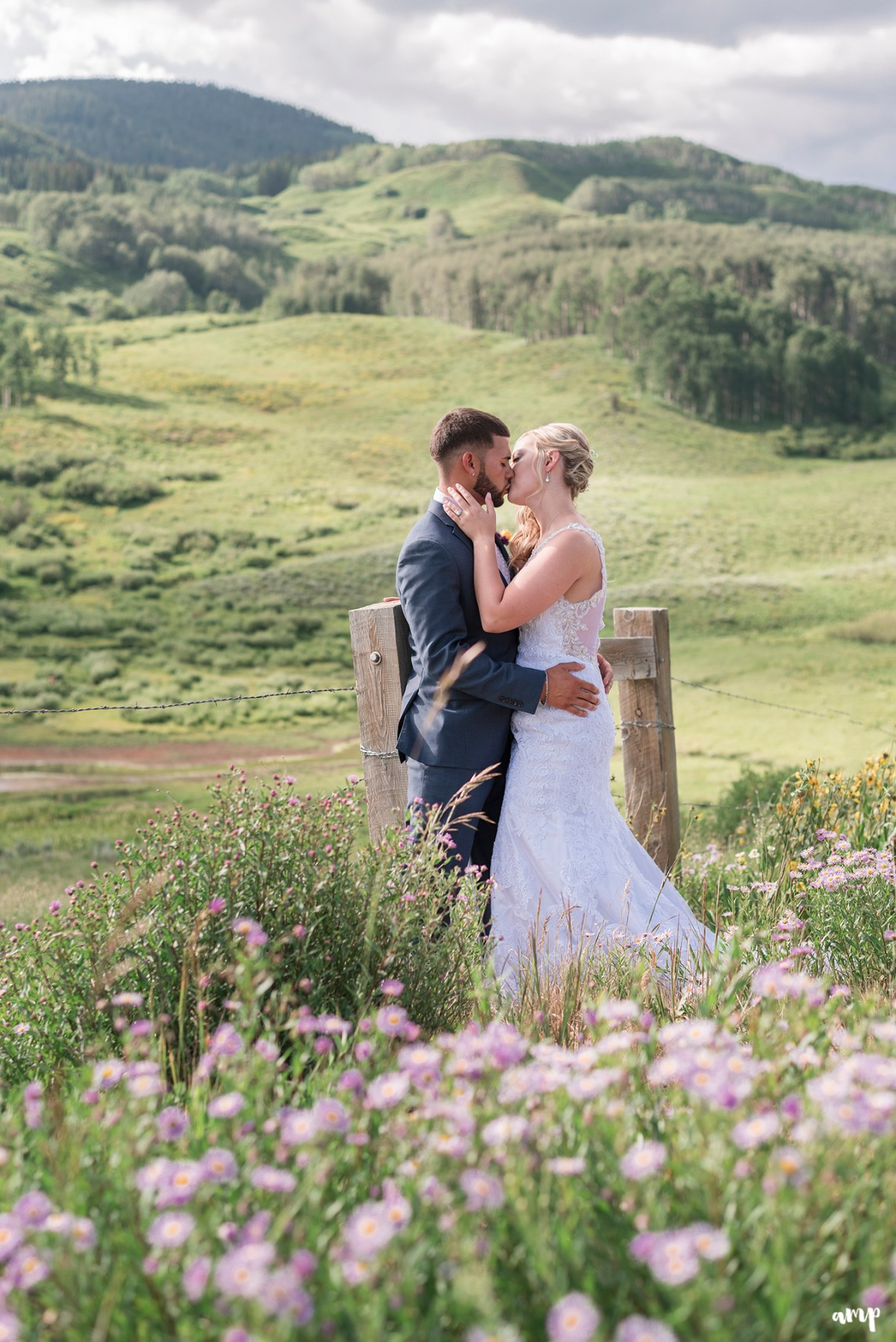 Bride and groom sharing a kiss among the wildflowers with mountains in the distance