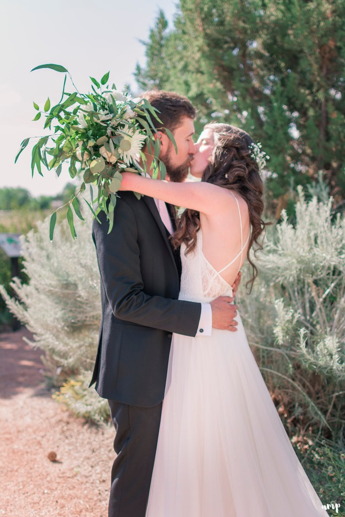 Bride and groom kissing in the botanic gardens