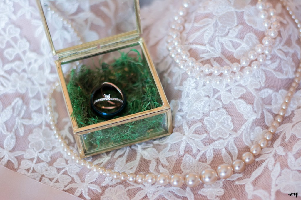 Wedding rings in antique gold and glass ring box atop lacy wedding dress and pearls