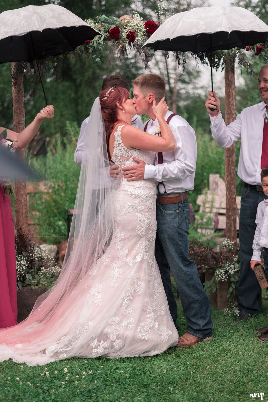 Bride and groom's first kiss in the rain