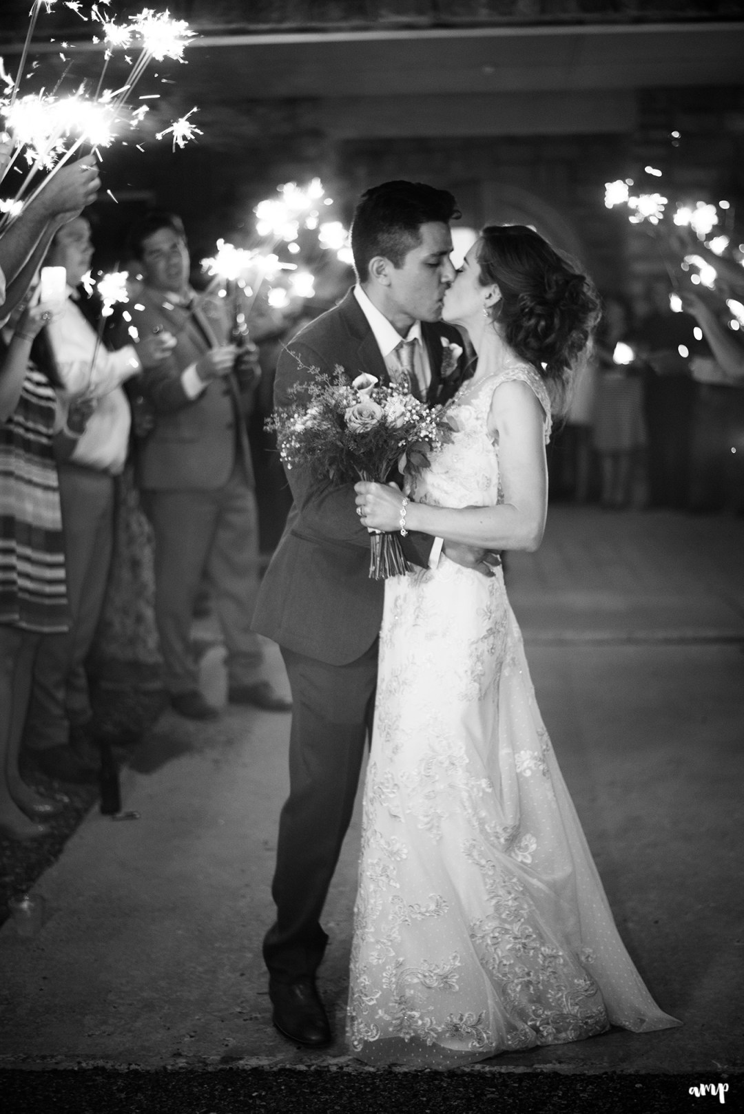 Bride and groom share a kiss during their sparkler exit
