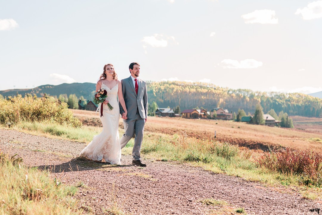 Bride and groom walk through the fall foliage at their Fall Wedding in Crested Butte at the Mountain Wedding Garden | amanda.matilda.photography