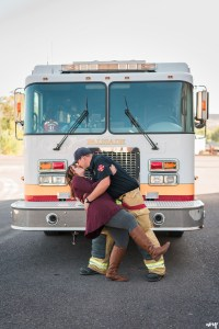 Couple being dipped for a kiss in front of a fire truck