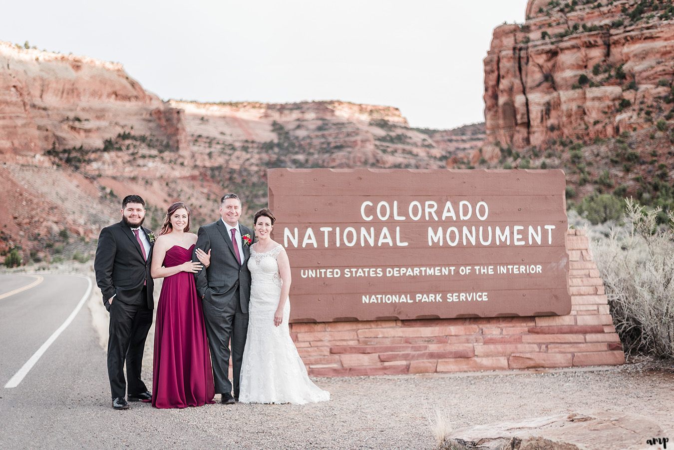 Full elopement group beside Colorado National Monument park sign