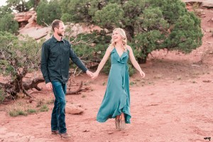 Dylan and Lexi walk hand-in-hand through the juniper trees of the Colorado National Monument for their engagement photos