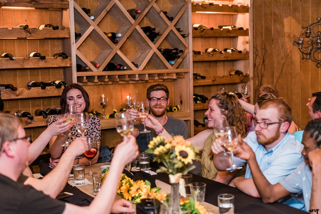 The group shares a toast at the Wine Dive