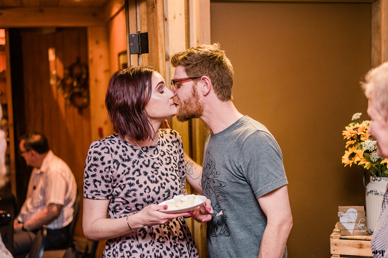 Ben and Courtnee share a kiss after cutting the cake at the Wine Dive in Wichita