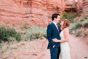 Blake and Carrie cuddle amid a red rocks canyon in Gateway