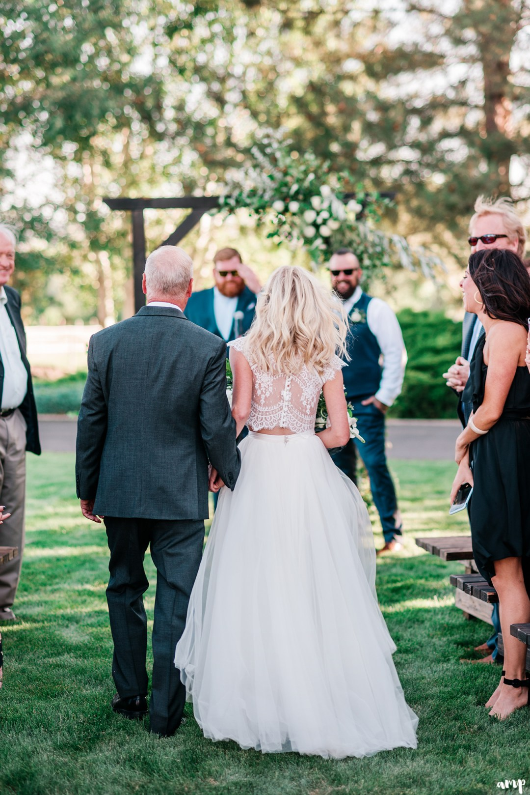 Shot of Beth and her dad walking down the aisle from behind | Grand Junction Backyard Wedding | amanda.matilda.photography