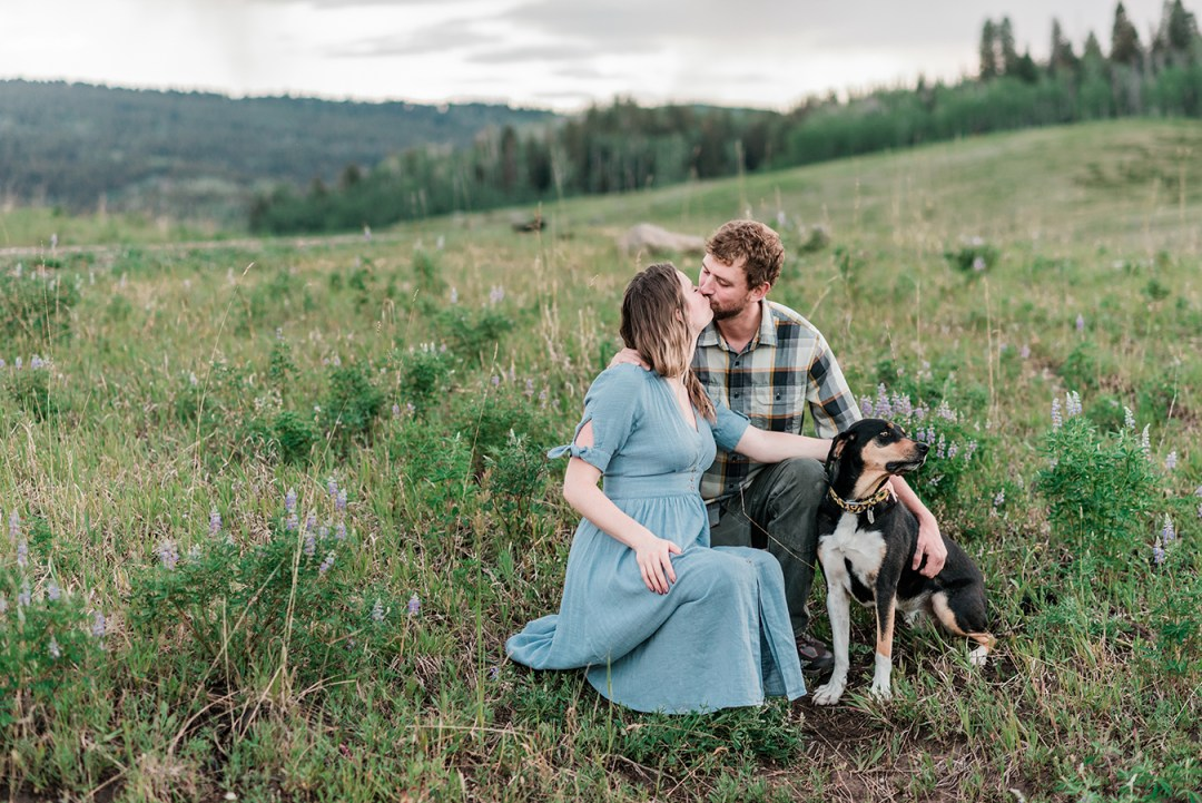 Annie & Taylor's dog looks away while the two kiss during their Glenwood Springs engagement photos