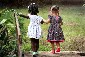 2 young black girls walking a boardwalk while holding hands