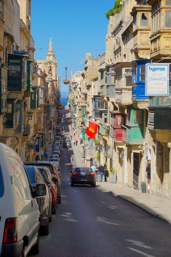 Hills and streets of Valletta Malta with colorful balconies and the Mediterranean Sea beyond.