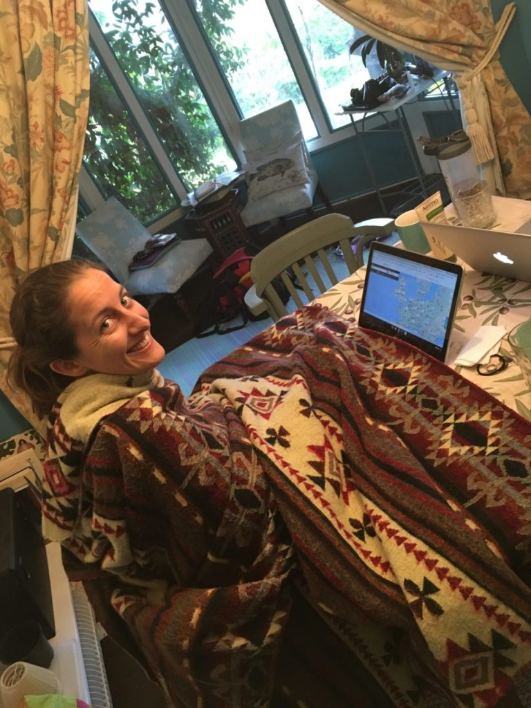 American expat blogger Amanda Walkins working on her computer in a cold room