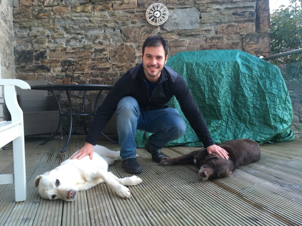 Jonathan Clarkin, housesitter with TrustedHousesitters, crouching outside on a deck while petting two Labrador retrievers during a dogsit
