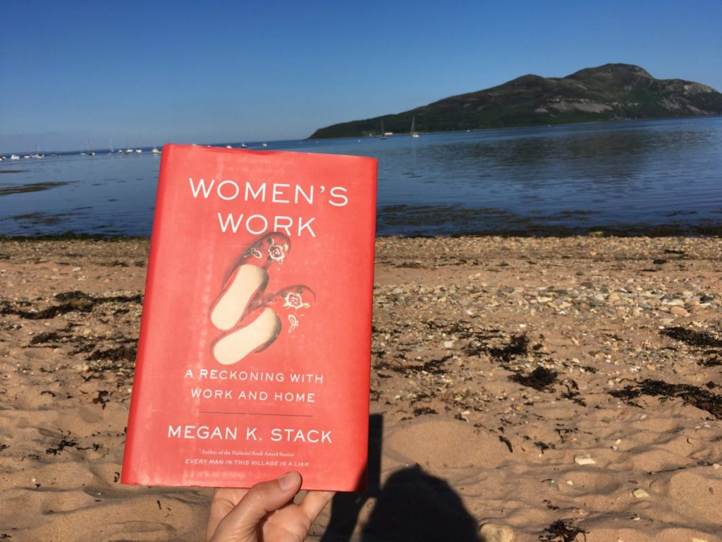 Women's Work, a book by Megan K Stack held up on a sunny day at the beach on Isle of Arran Scotland