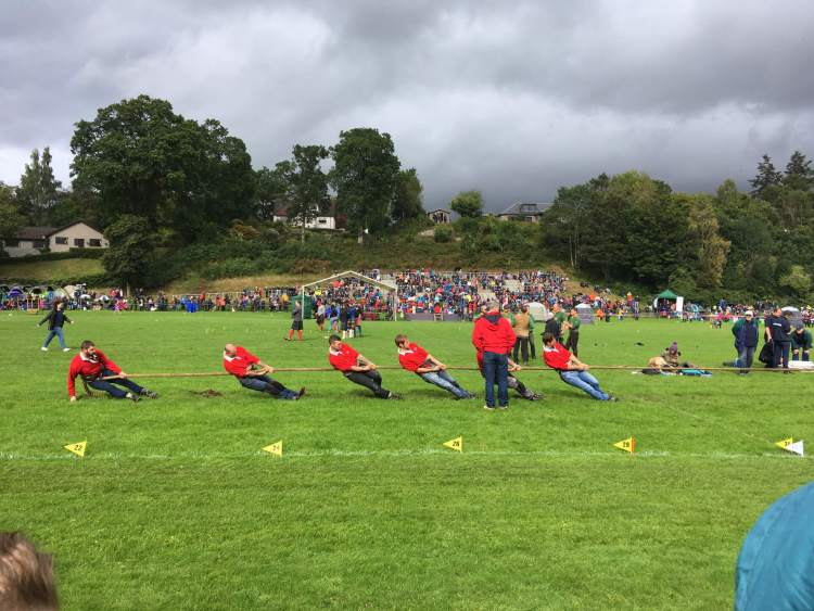 Men in red shirts compete in the tug-of-war at the Pitlochry Highland Games