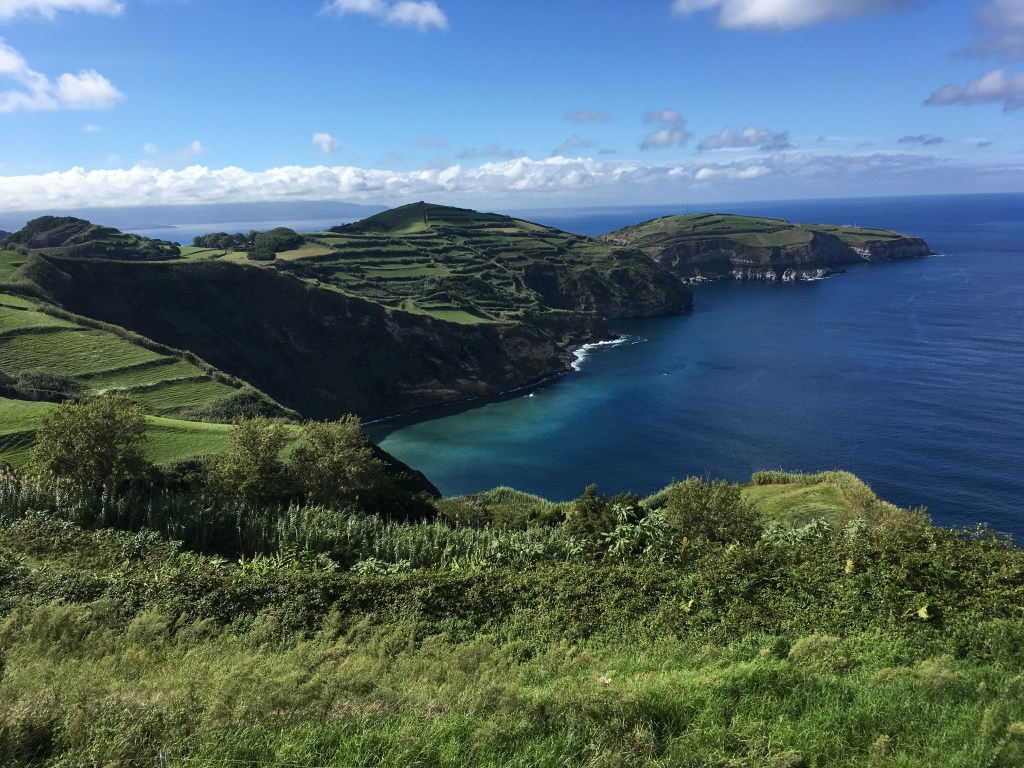 View from a lookout point on Sao Miguel Island in the Azores with vibrant hues of green leading into the blue sea