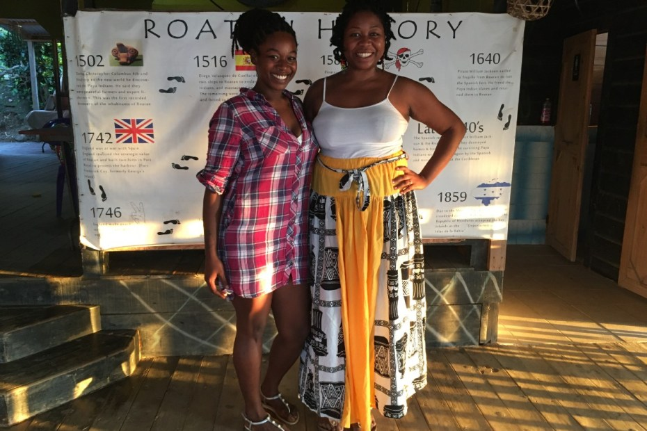 Nora and Audrey Flores of the Flamingo Cultural Center in Roatan standing in front of the history of Roatan timeline