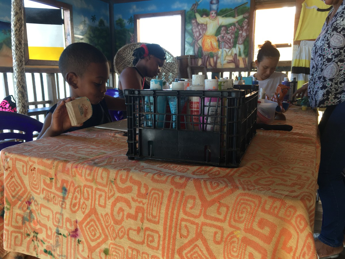 Women and kids painting at a table in Punta Gorda Roatan