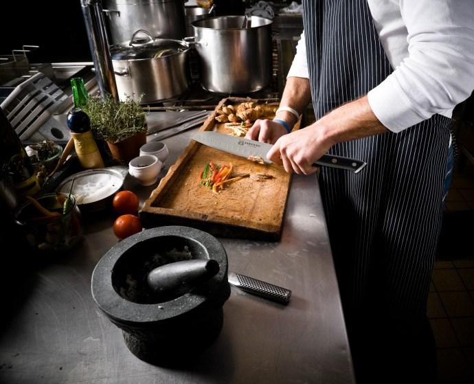 Kurouto Kitchenware Santoku Knife Chopping Vegetables in a Restaurant Kitchen