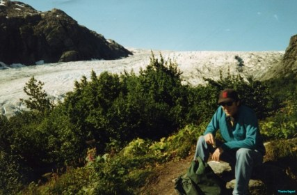 Dan, with baseball cap, perches on a stone to enjoy a picnic on a ridge near to a large glacier tumbling down hill