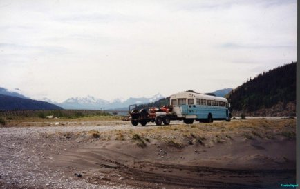 A bus of the type used commonly in Alaska, with lots of small side windows and corrugated steel sides