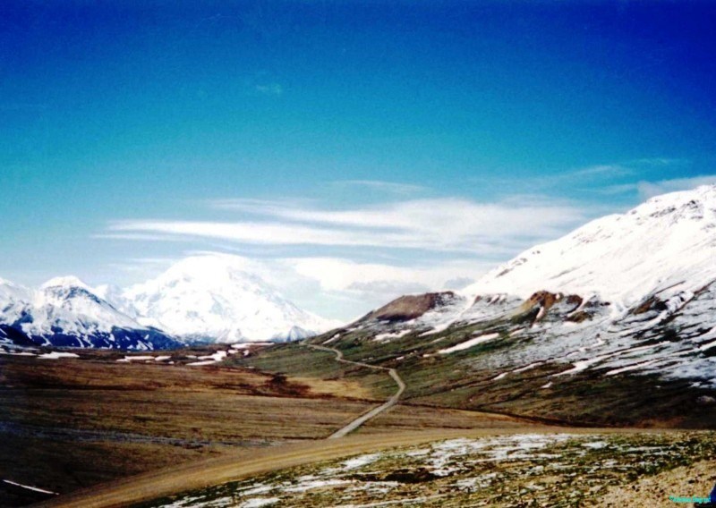 A low green valley stretches beneath partly wooded mountains, rising to snow scattered slopes. In the distandce the bulk of Mount McKinley (Denali) dominates the skyline, some 50 miles away