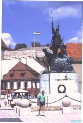 A Hungarian flag flies atop a fortress battlements. In the foreground a defiant defender is memorialised in a warlike statue