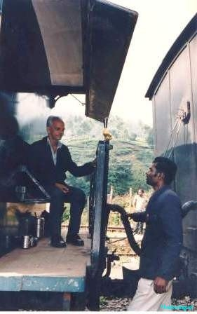 A train guard seated at his station, confers with a colleague