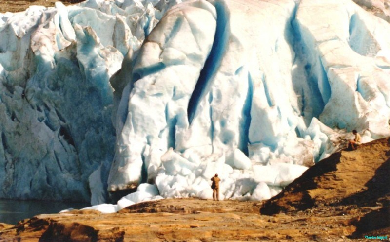 A person stands in awe of a Norwegian glacier which dwarfs them