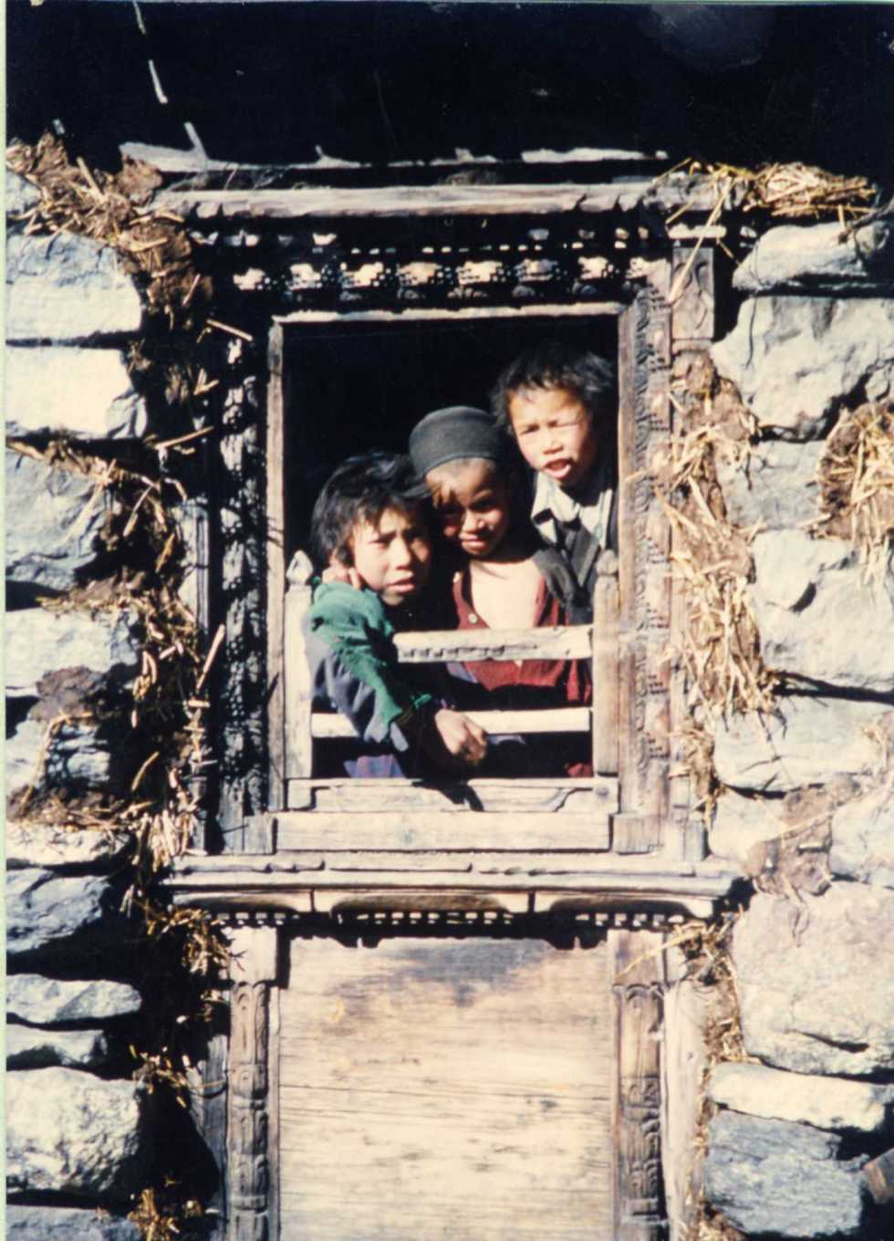 Curious kids peering from a house window in Langtang