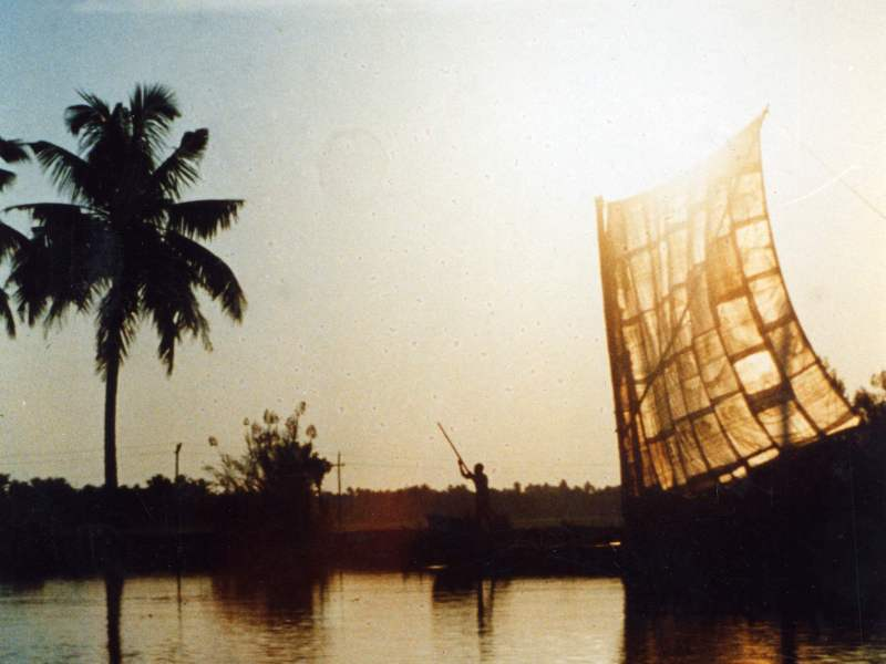 Cargo boat on Kerala canals, India, the sail made of sacks stitched together is lit through by a lowering sun