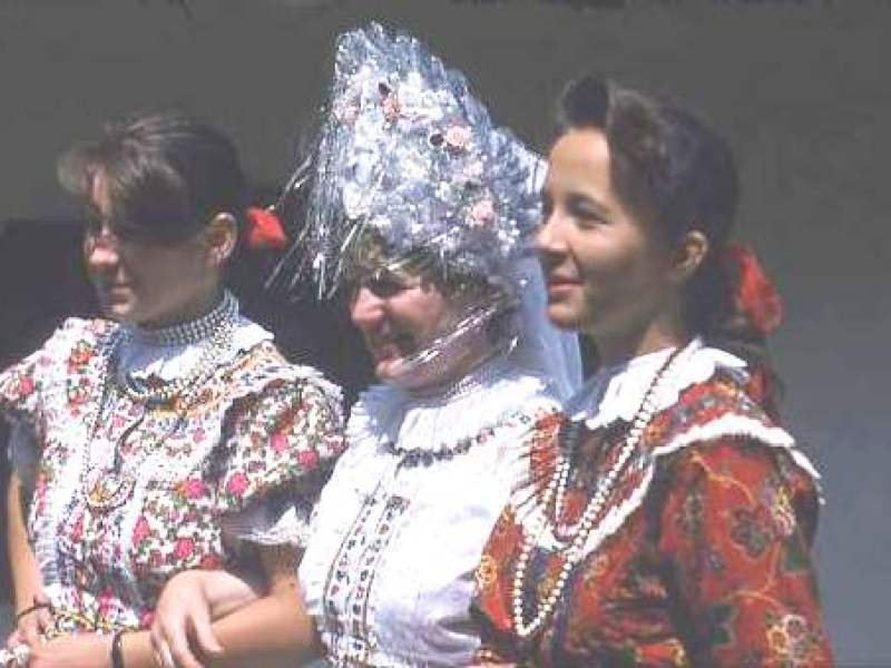 Hungarian women in traditional dress, with lots of frills and high headdress