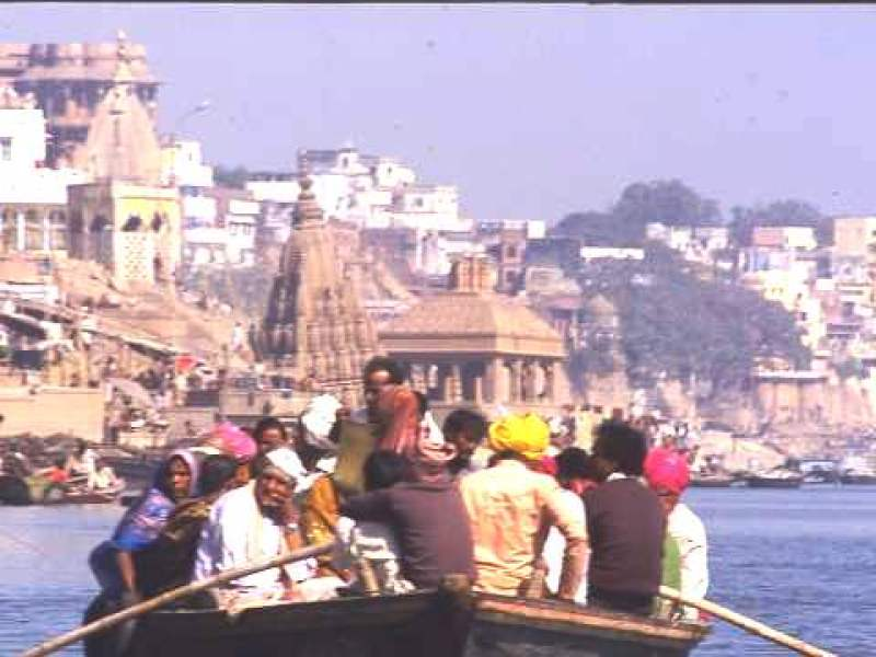 Boat trip, Varanasi, a crowd of devotees being rowed along the Ganges riverbank, where bathing steps and temples crowd together