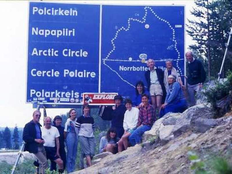 Swimmers posing by the Arctic Circle sign in Sweden - a lake lies across the invisible line