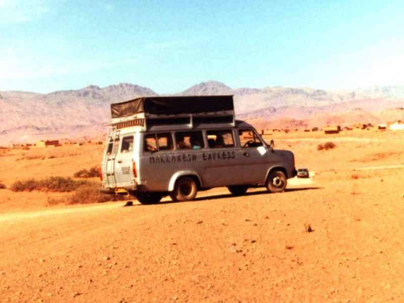 A minibus with large roof rack for camping gear speeds through the sandy terrain to the south of the Atlas mountains
