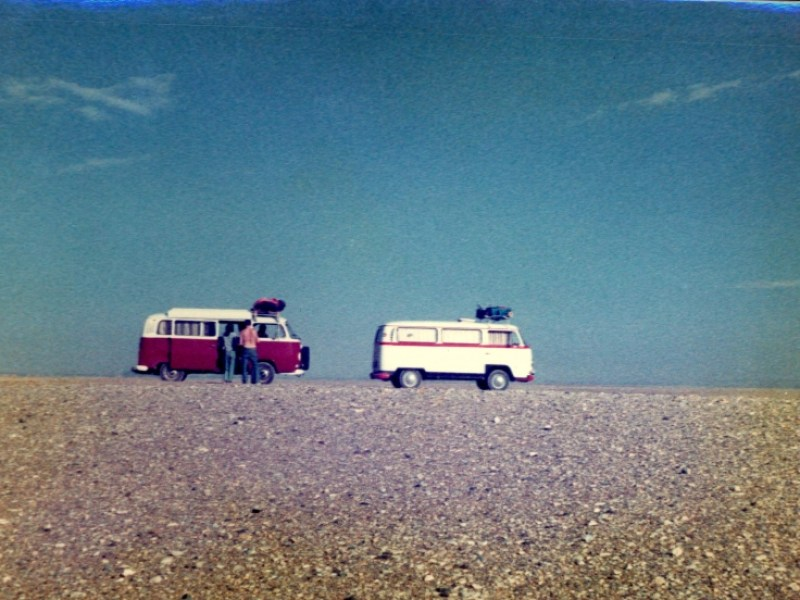 Two volkswagen campervans are apparently perched exactly on the horizon where a dry stony desert plain meets the unblemished skies