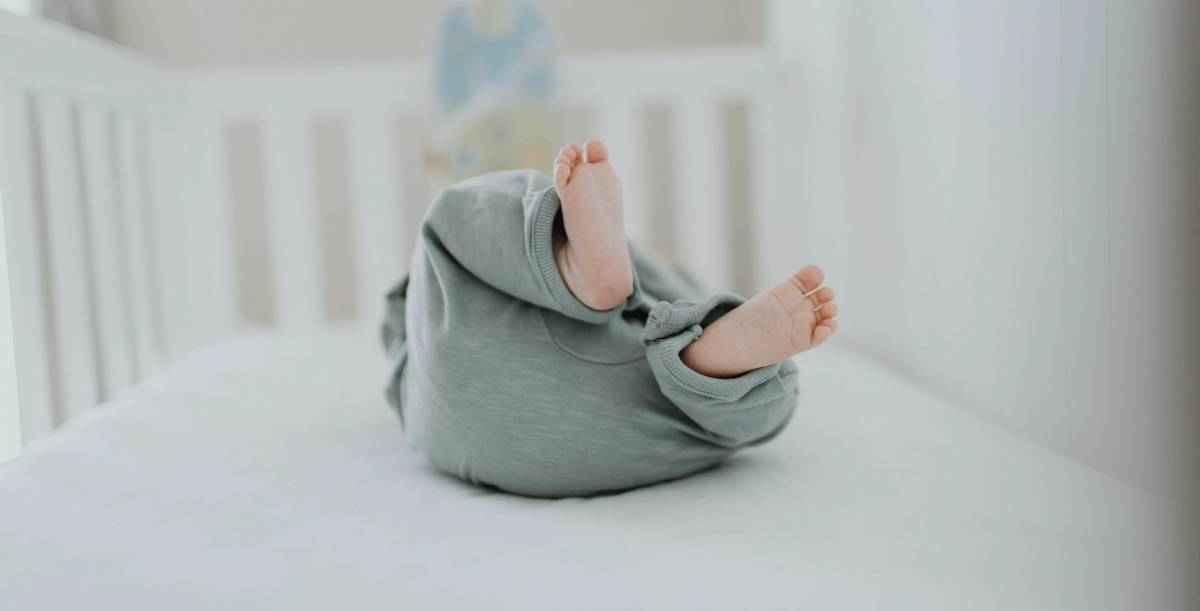 The Canadian Paediatric Society recommends little ones sleep in the same room as their parents until six months to promote nighttime breastfeeding and reduce the risk of SIDS.