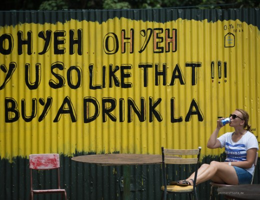 """huge yellow sign with black letters painted on a side of a dilapidated building. It says """"oh yeh, oh yeh, y u so like that buy a drink lah"""". I'm sitting comfortably on a chair in front of it, drinking a can of cold Tiger beer. The photo was taken on Pulay Ubin island just off the coast of Singapore."""